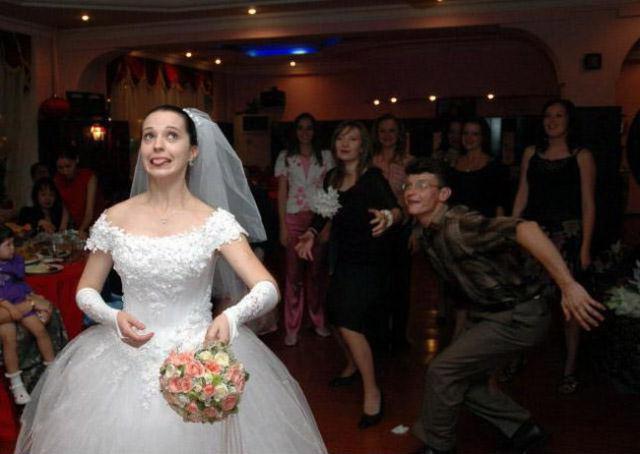 Eine Braut will ihren Brautstrauß zu den Junggesellinnen werfen. Ein junger Mann drängelt sich ins Bild, er will den Strauß scheinbar fangen.