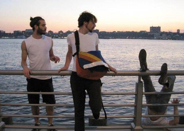Drei Männer wollen sich auf einem Geländer an einem See oder Fluß fotografieren lassen. In dem Moment als das Foto geschossen wird, stürzt einer der Männer rückwärts ins Wasser.