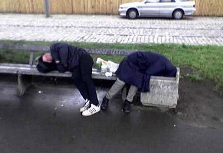Zwei Menschen liegen auf einer Bank und schlafen. Die Frau hat ihren Kopf in den Mülleimer gelegt.
