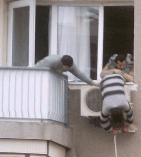 Ein Mann hält einen anderen aus dem Fenster, damit er eine Klimaanlage reparieren kann.