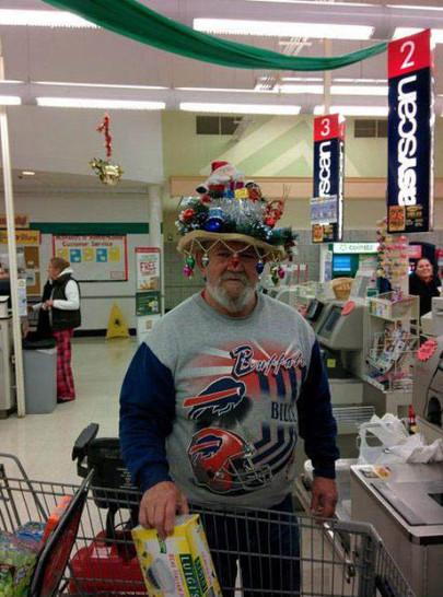 Ein Mann trägt einen Hut, der mit Weihnachtsschmuck und einem Weihnachtsmann geschmückt ist beim Einkaufen.