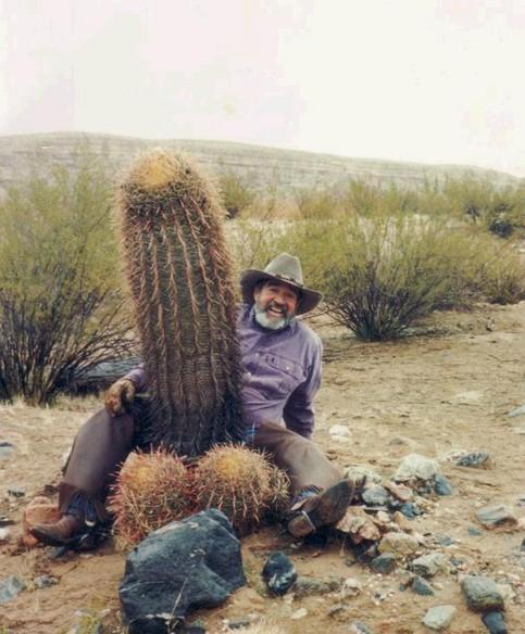 Ein Mann hat einen Kaktus in Penis-Form zwischen seinen Beinen.