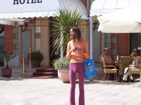 Ein Mann steht mit einer hautengen pinken Leggings und einem orangefarbenen Oberteil vor einem Hotel.
