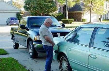 Ein Mann uriniert in den Tank eines Autos.