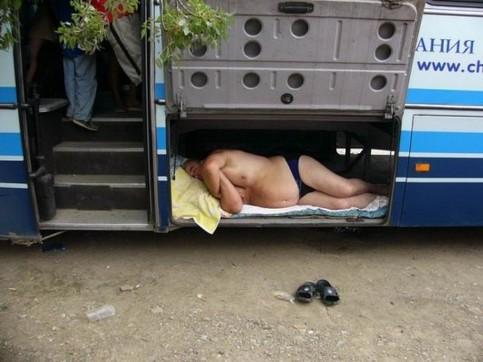 Ein Mann schläft im Gepäckraum eines Busses.