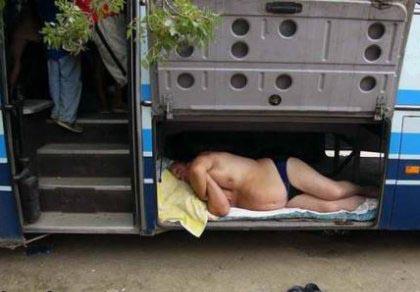 Ein Mann schläft in Unterhose im Kofferraum eines Buses.