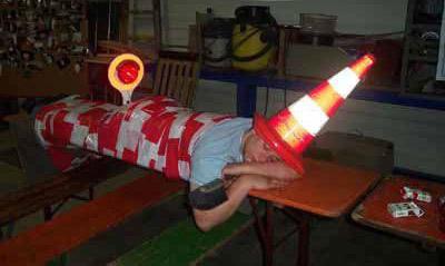 Ein Mann schläft offensichtlich betrunken auf einer Bank. Man hat ihn mit Absperrband an die Bank gefesselt, Eine Pelone auf den Kopf gesetzt und eine Polizeikelle an den Hintern geklebt.