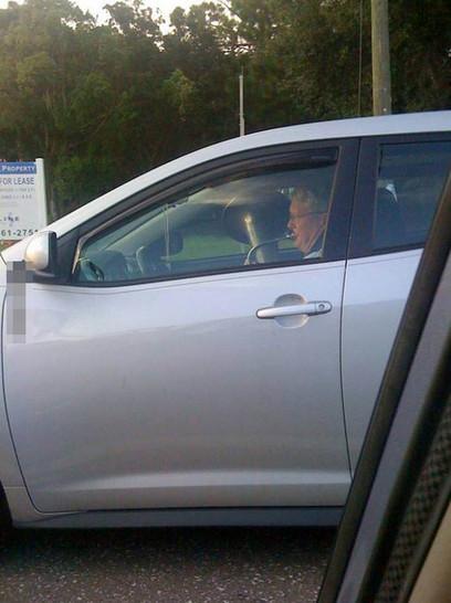 Ein Mann sitzt in einem Auto und spielt Tuba.