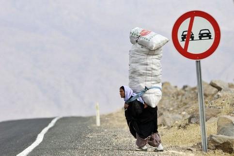 Ein Mann steht am Straßenrand in einer verlassenen Gegend und trägt eine riesige Last auf seinem Rücken.