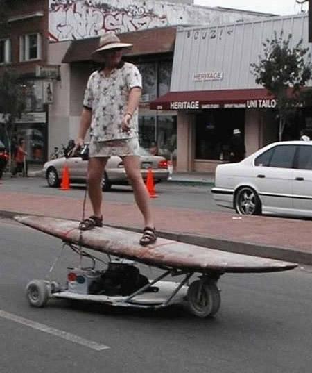 Ein Mann steht auf einem Surfbrett mit Unterbau, der Rollen hat, und fährt damit auf einer Straße.