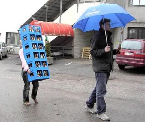 Ein Mann trinkt ein Bier unter einem Regenschirm, während seine Frau sechs Kisten Bier schleppt.