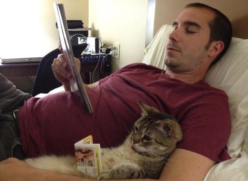 Ein Mann liest in einer Zeitschrift, in seiem Arm liegt eine Katze und scheint ebenfalls zu lesen.