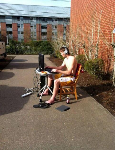 Ein junger Mann sitzt nur mit kurzer Hose bekleidet im Freien vor einem PC, den er auf einem Tisch aufgebaucht hat. Er scheint ein Computerspiel zu zocken.