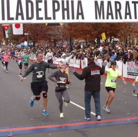 An der Ziellinie eines Marathons steht ein Mann, der die Läufer abklatscht. Ein Läufer will dies tun und schlägt dabei mit seiner Hand der neben ihm laufenden Frau ins Gesicht.