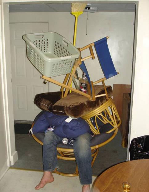 Ein Mann auf einem Stuhl ist mit lauter Krempel voll gestellt.