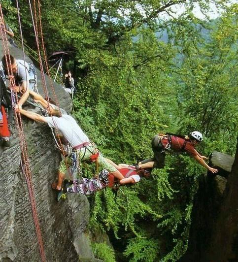 Beim Klettern bilden die Kletterer eine Brücke, über die zwischen zwei Felsen geklettert wird.