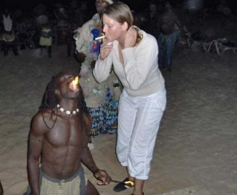 Eine Frau zündet sich mit dem Feuer eines Feuerspuckers eine Zigarette an.
