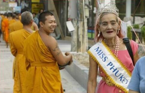 """Eine alte, häßliche Frau trägt eine Schärpe: """"Miss Phuket""""."""