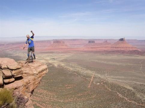 Ein Mann fährt auf einem Felsvorsprung mit einem Einrad.