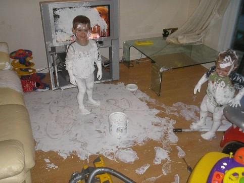 Zwei Kinder haben einen Eimer Farbe im Wohnzimmer und über dem Fernseher entleert.
