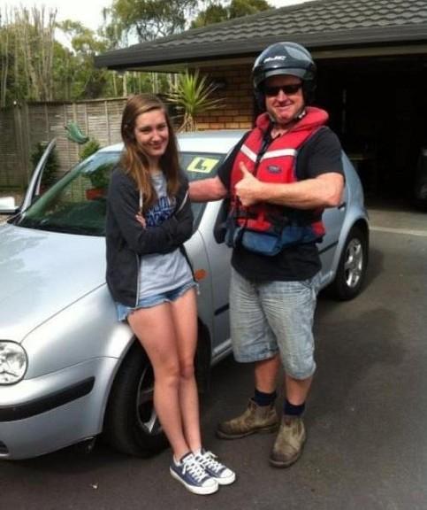 Ein Mann will mit Schutzweste und Helm als Beifahrer in einem Auto mit einer jungen Fahrerin fahren. Offensichtlich ist sie eine Fahrangängerin und er erlaubt sich einen Scherz
