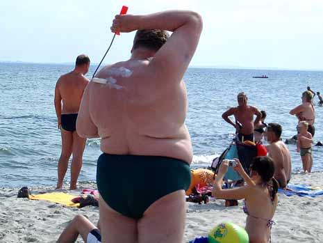 Ein Mann cremt seinen Rücken am Strand mit einer Malerrolle ein.