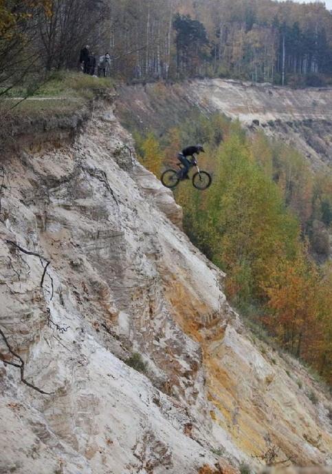 Ein Fahrradfahrer mit einem Mountain Bike stürzt sich einen steilen Abhang hinunter.