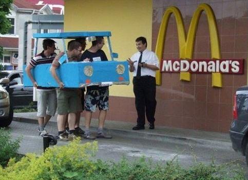 Vier junge Männer wollen in einem McDrive etwas zu essen holen. Dazu haben sie sich ein Auto aus Pappe gebaut, mit dem sie in er Autoschlange stehen. Ein McDonalds-Mitarbeiter diskutiert dabei mit ihnen.