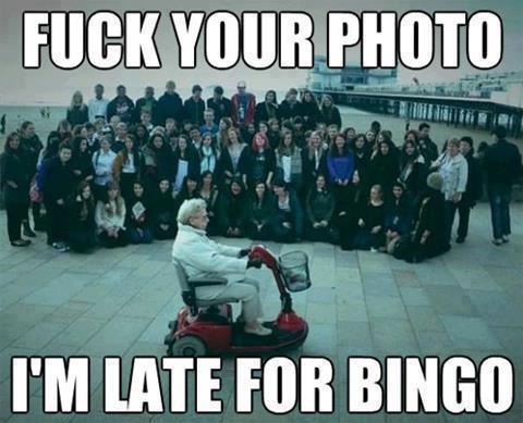 """Eine Frau fährt mit einem Elektro-Rollstuhl über einen Platz, auf dem gerade ein Gruppenfoto gemacht wird. Die Frau fährt direkt ins Bild hinein, dazu steht: """"Fuck your Photo. I am late for Bingo"""