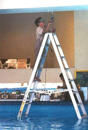 Ein Mann hat eine Leiter in einen Swimmingpool gestellt und bohrt auf dieser in der Decke.