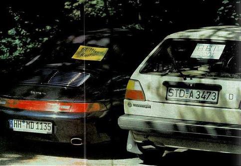 """Zwei Autos stehen nebeneinander, im Golf II klebt ein Schild """"ABI"""", im Porsche """"Mittlere Reife""""."""