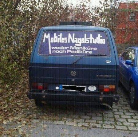 """Auf der Rückscheibe eines VW-Bully steht """"Mobiles Nagelstudio - weder Maniküre noch Pediküre""""."""