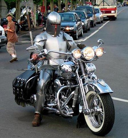 Ein Mann in Ritterkostüm auf einem Motorrad.