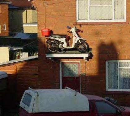 Ein Roller ist auf einem Dach über einer Tür geparkt.