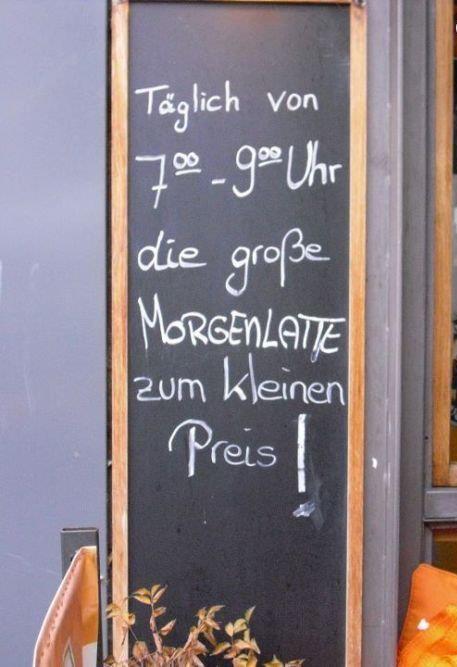"""Auf einer Tafel vor einem Café ist ein Angebot für eine """"Morgenlatte"""" zu lesen. """"Die große Morgenlatte zum kleinen Preis""""."""