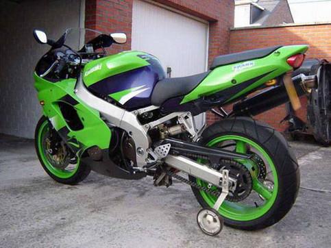Ein Kawasaki-Motorrad, an dem Stützräder montiert sind.