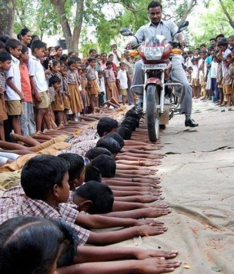Ein Mann fährt in Indien mit einem Motorrad über eine Reihe Hände, die knieende Kinder ausstrecken.