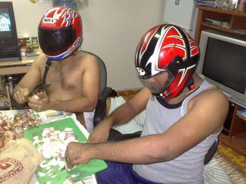Zwei Männer schneiden Zwiebeln. Dabei tragen sie Motorradhelme, um sich vor dem Weinen zu schützen.