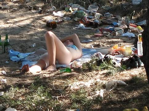 Eine Frau liegt an einem Strand zwischen lauter Müll.