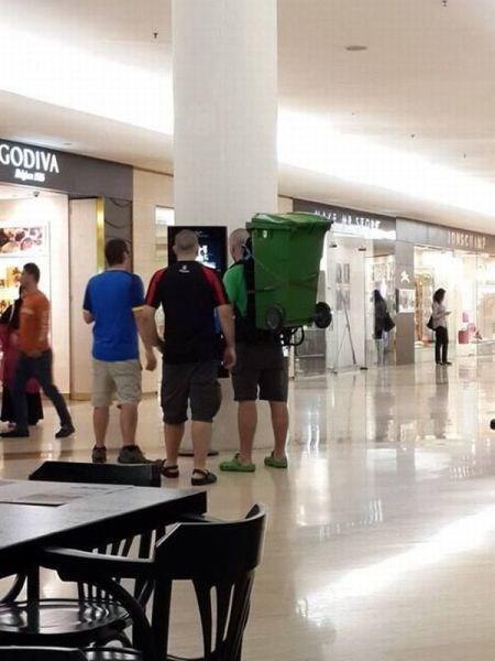 Ein Mann trägt eine große grüne Tonne auf seinem Rücken, als eine Art Rucksack.
