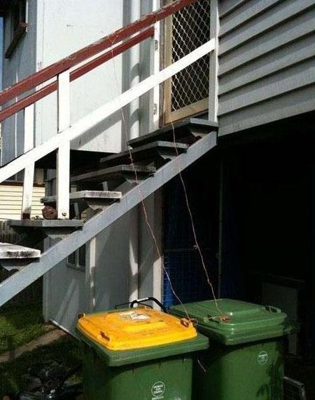 Zwei Mülltonnen stehen unter einer Treppe. An beiden ist an der Klappe ist ein Seil befestigt. So kann man von der Treppe aus die Tonnen öffnen und den Müll von oben in die Tonne werfen.