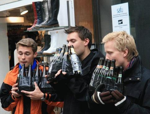 Drei Männer blasen auf Flaschen Musik.