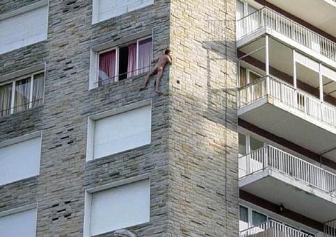 Ein nackter Mann ist aus einem Fenster geklettert und klammert sich an der Hauswand fest.