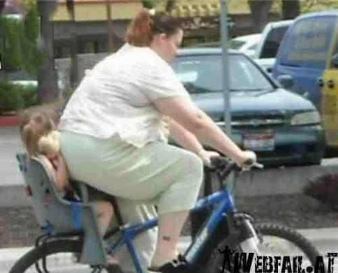 Eine sehr korpulente Frau fährt Fahrrad. Im Kindersitz sitzt ihre kleine Tochter. Durch ihren üppigen Hintern ist kaum noch Platz für ihre Tochter im Kindersitz.