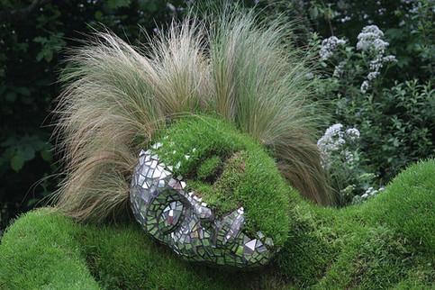 Ein aus Klinkern, Moos und Gras gebildetes Gesicht.