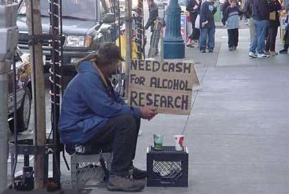 """Ein Bettler hat ein Schild """"Need cash for alcohol research"""""""