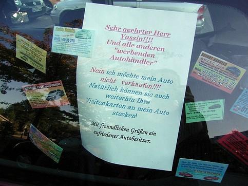 """Ein Zettel in einem Auto macht sich über die üblichen """"Wollen Sie ihr Auto verkaufen?""""-Visitenkarten lustig."""