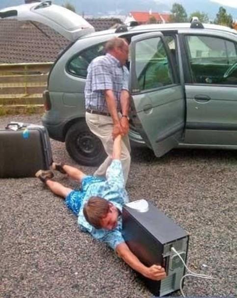 Ein Mann zerrt einen Jungen in ein Auto. Dieser klammert sich an seinem Computer fest.