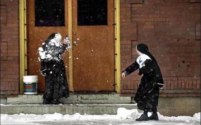 Zwei Nonnen machen eine Schneeballschlacht.