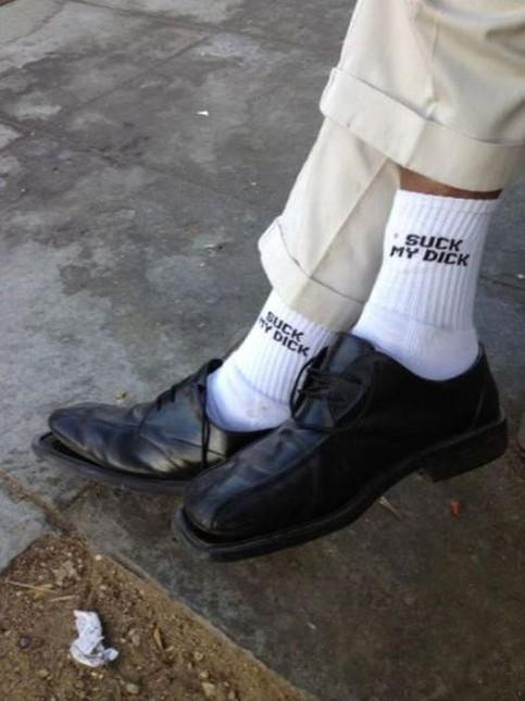 Großaufnahme der Beine und Füße eines Mannes. Die Lederschuhe sind kaputt und auf den weißen Tennissocken steht ein obszöner englischer Spruch.